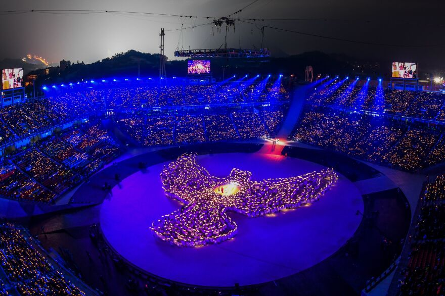 More than 1,200 people, including 1,000 residents of Gangwon province, form the shape of a dove out of candlelight during the opening ceremony.