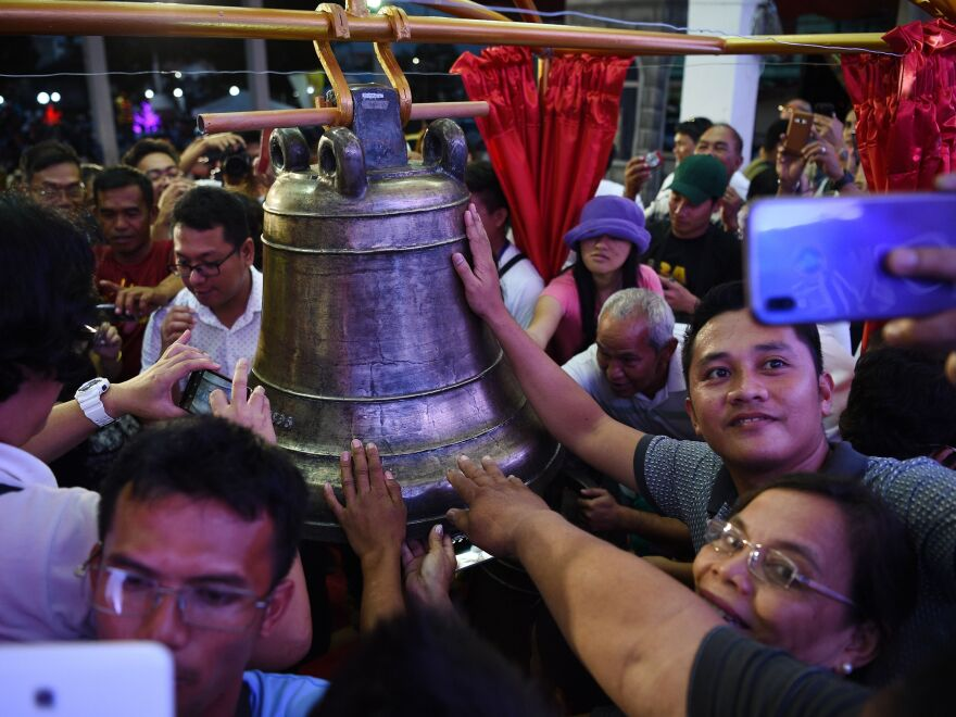 Residents take photos and try to touch one of the three Balangiga church bells after a ceremony returning them to the church in the town of Balangiga in the Philippines on Dec. 15, 2018.