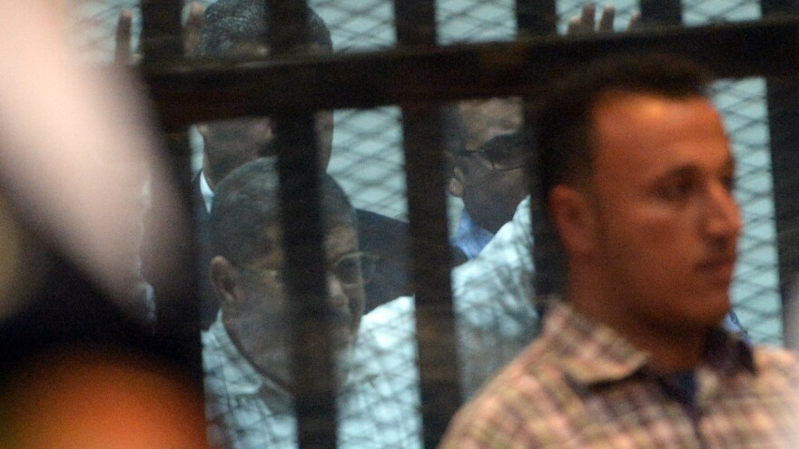 Egypt's former President Mohammed Morsi gestures from the defendants' cage during his trial in Cairo on Tuesday. An Egyptian court sentenced the ousted leader to 20 years in prison for abuses of protesters.