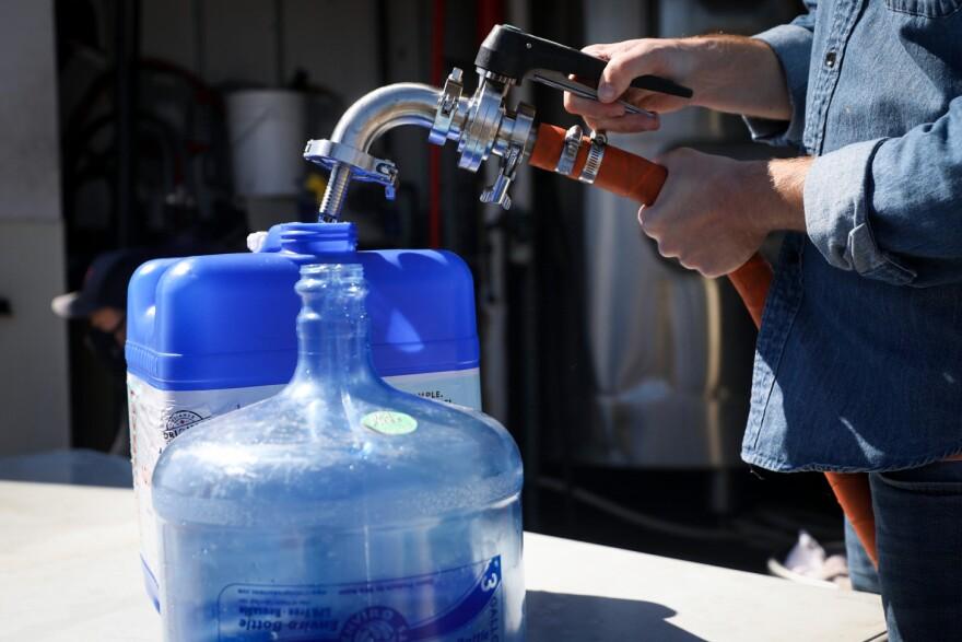 Empleado llena dos contenedores de plástico con agua.