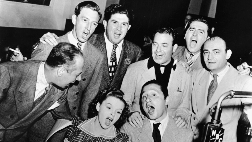 Composer Harold Arlen (sitting, right) joins Judy Garland, Bert Lahr (far left), Ray Bolger (back row, left) and various executives for a<em> Wizard of Oz</em> sing-along in the NBC radio studio, circa 1939.