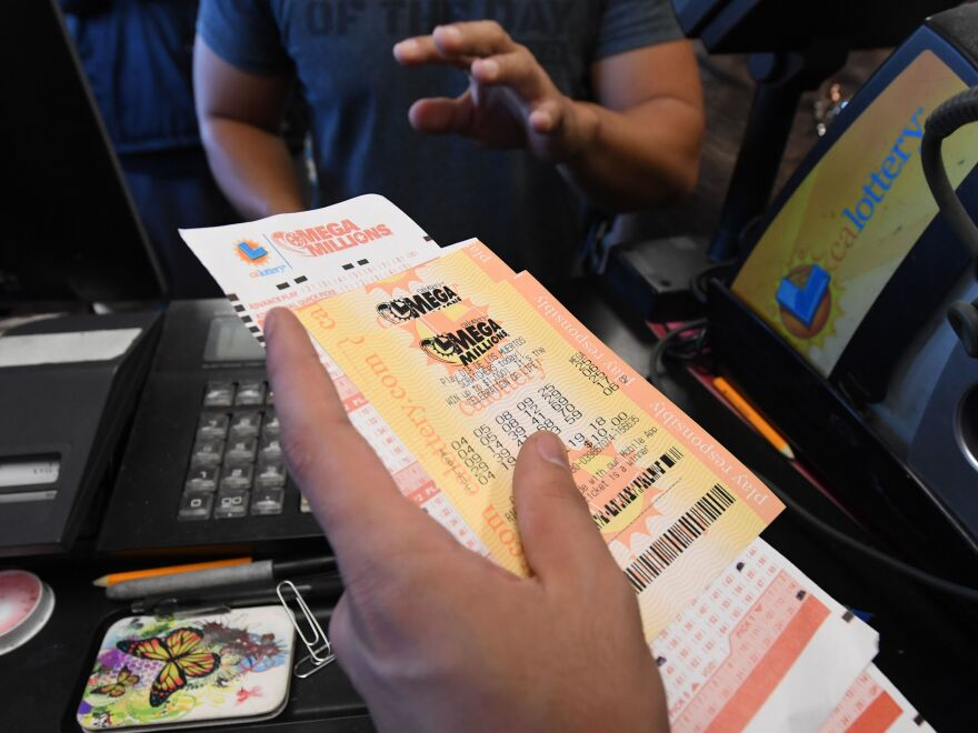 A man in Torrance, Calif., buys a Mega Millions ticket hours before the drawing on Friday evening. No one won that drawing, and the jackpot went up to $1.6 billion.