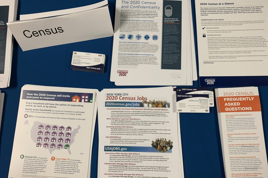 Flyers and pamphlets about the 2020 census are displayed on a table.