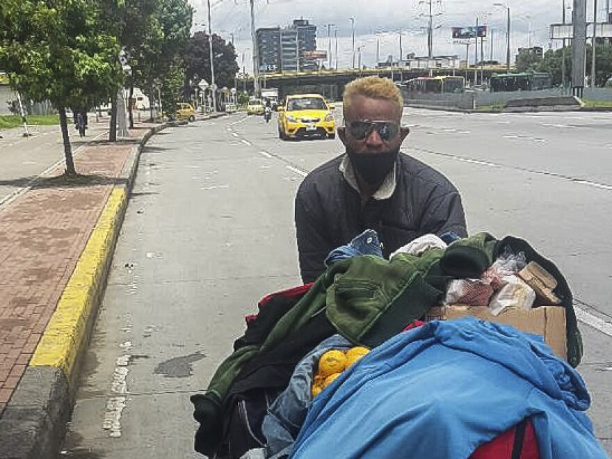 Felix Ruiz, a Venezuelan migrant, pushes a cart along the highway out of Bogotá.