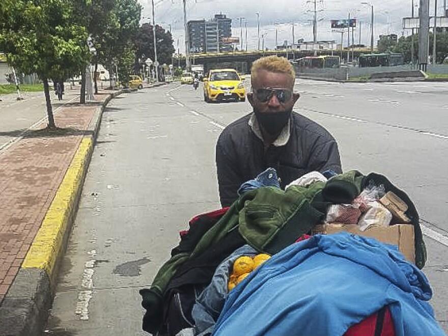 Felix Ruiz, a Venezuelan migrant, pushes a cart along the highway out of Bogotá.