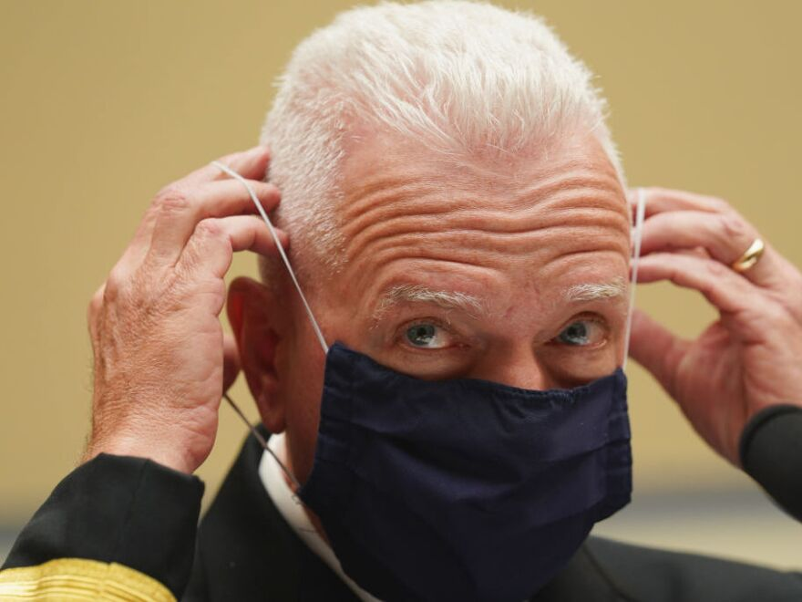 Adm. Brett Giroir, assistant secretary for health in the Department of Health and Human Services, adjusts his face mask while testifying this month before a House subcommittee on the coronavirus crisis.