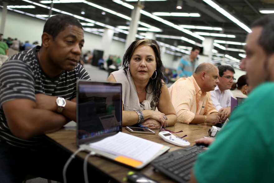 Jose Ramirez and Mariana Silva speak in December with Yosmay Valdivia (right), an agent from Sunshine Life and Health Advisors, at the Mall of the Americas in Miami about plans available from the Affordable Care Act.