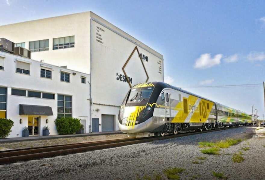 A yellow Brightline train passing a building in Miami