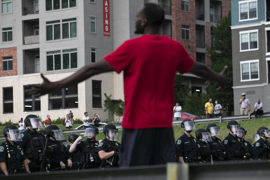 A man stands with his arms outstretched in front of a line of Austin police officers.