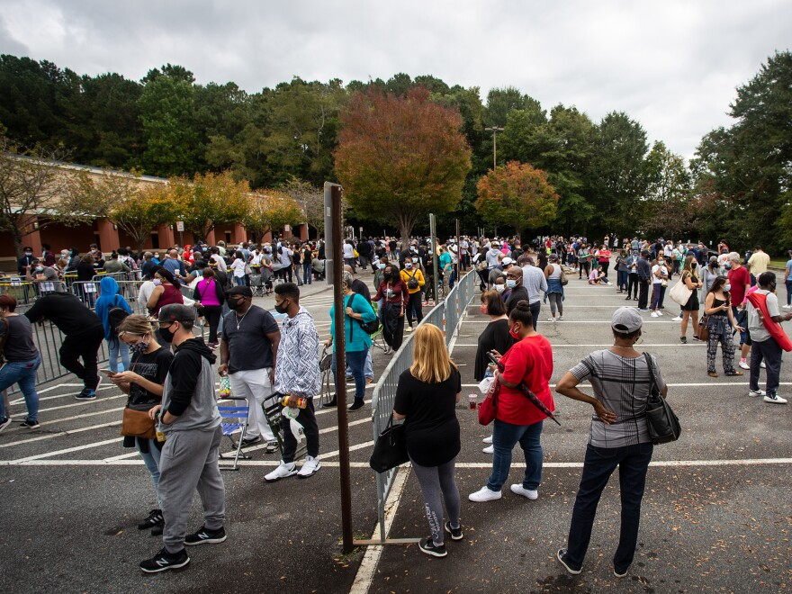 Hundreds of people wait in line for early voting on Oct. 12, 2020, in Marietta, Ga. Eager voters have waited six hours or more in the former Republican stronghold of Cobb County, and lines have wrapped around buildings in solidly Democratic DeKalb County.