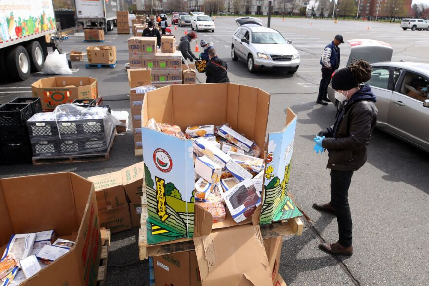 A volunteer prepares to load food into a car at a mobile pantry April 14, 2020 in Detroit, Michigan. The organization distributes food throughout the metro area, which has seen an uptick in demand due to the COVID-19 pandemic. (Gregory Shamus/Getty Images)