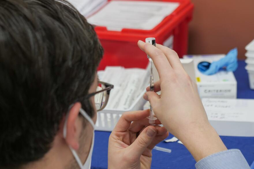 A woman with short hair, dressed in a blue, long sleeve shirt, draws liquid into a syringe from a vial