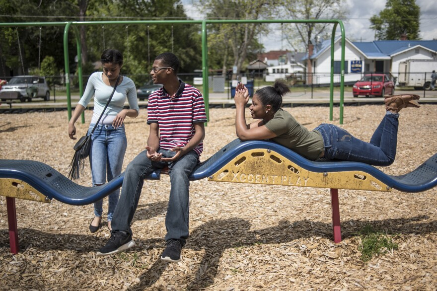 Gordon talks with friends Brittany Bloome (left) and Chanel Smith at a park down the street from the school. The seniors used their final block of the school day to get outside and pick up a late lunch from local businesses.