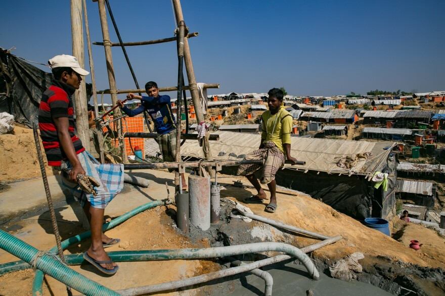 """Two men operate what's called a """"donkey pump"""" as they drill a new water well in the Balukhali refugee camp. Aid groups are providing funds and materials to dig deeper wells that are less likely to get contaminated during seasonal flooding."""
