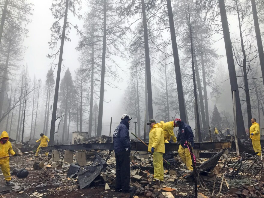 Volunteers search a mobile home park in Paradise, Calif. Government scientists predict wildfires like the one that struck this community will contribute to billions in losses for the U.S. economy.