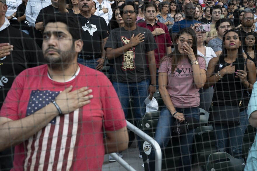 Attendees to Wednesday night's community memorial service in El Paso, at the Southwest University Park stadium stand for the national anthem.