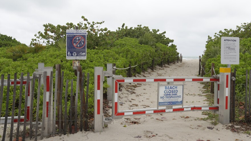 A locked gate blocks the path down to the shore in Miami's South Beach on Monday. While beaches remained closed in the area because of the coronavirus pandemic, the rain washed away plenty of outdoor plans, as well.