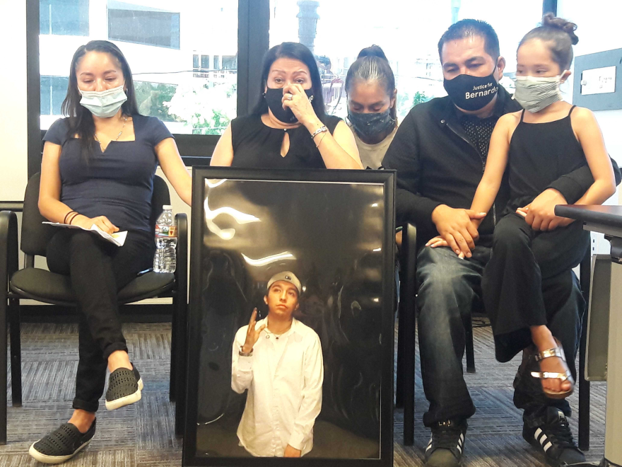 Photo of five people sitting, wearing masks and holding up a framed photo of a man