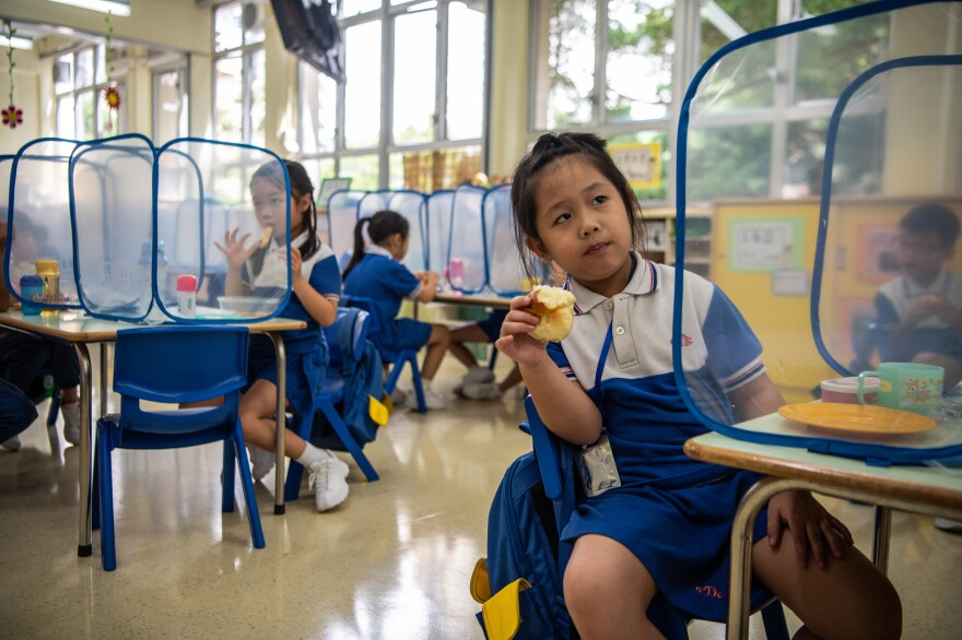 Kindergarten children eat their snacks behind plastic dividers at Tsung Tsin Primary School and Kindergarten.
