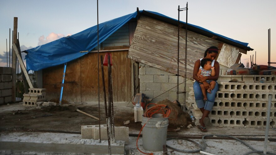 Isamar holds her 9-month-old baby Saniel at their makeshift home in San Isidro, Puerto Rico.