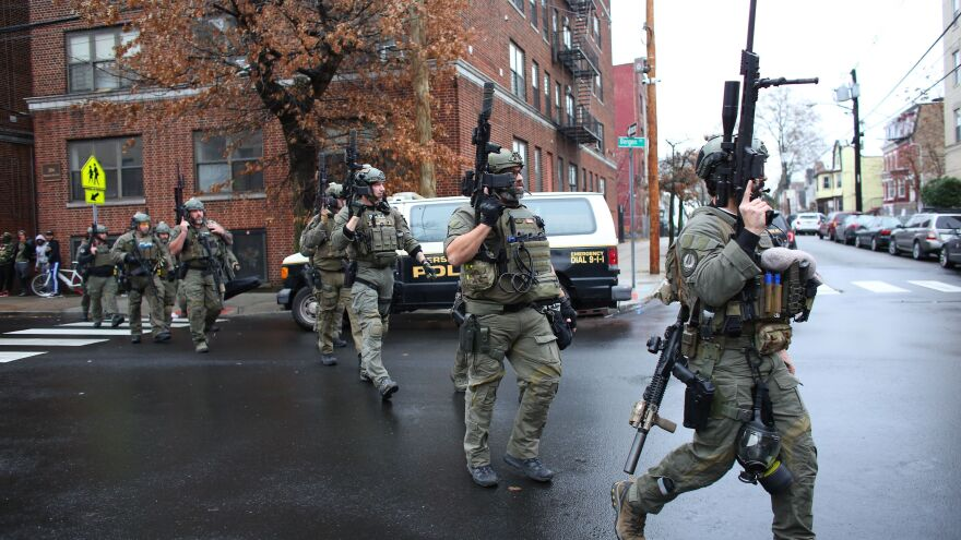 Police arrive at the scene of a shooting in Jersey City, N.J., Tuesday. There were two separate shooting incidents beginning at Bayview Cemetery and then later at a kosher market.