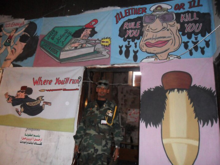 A soldier stands near anti-Gadhafi graffiti in Libya in 2011. The revolution that ousted Libya's longtime leader later that year resulted in a cycle of tribal and factional infighting, and a civil war that has essentially divided the country.