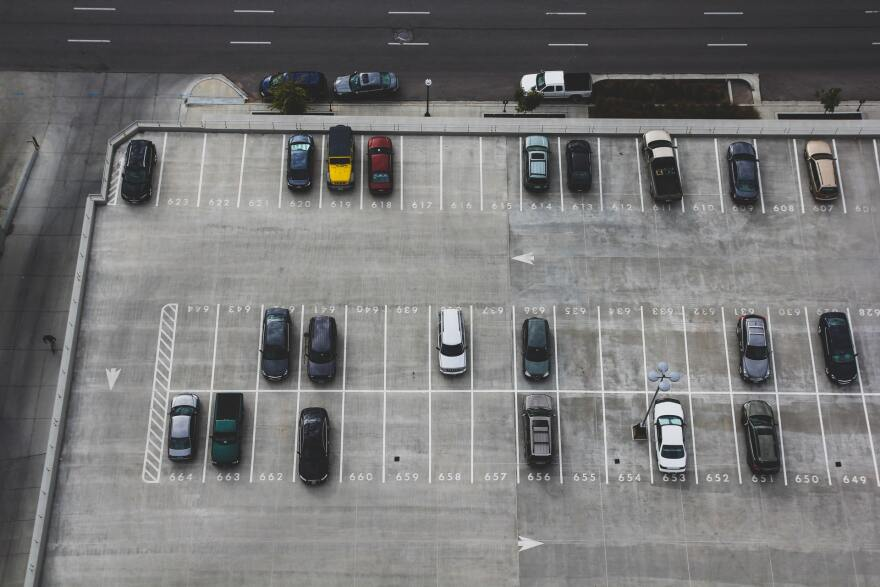 A bird's-eye view of cars parked among numbered parking spots in a lot abutting a city street.