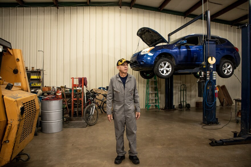Joe Ponce stands in a garage with a blue car lifted up behind him.