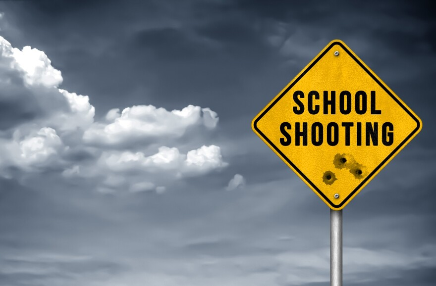 "Yellow road sign with ""School Shooting"" printed on it"