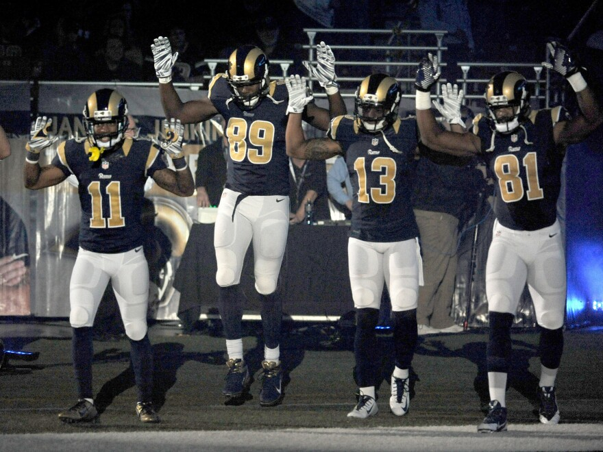 """Members of the St. Louis Rams raise their arms in a """"hands up, don't shoot"""" pose as they walk onto the field before an NFL football game against the Oakland Raiders."""