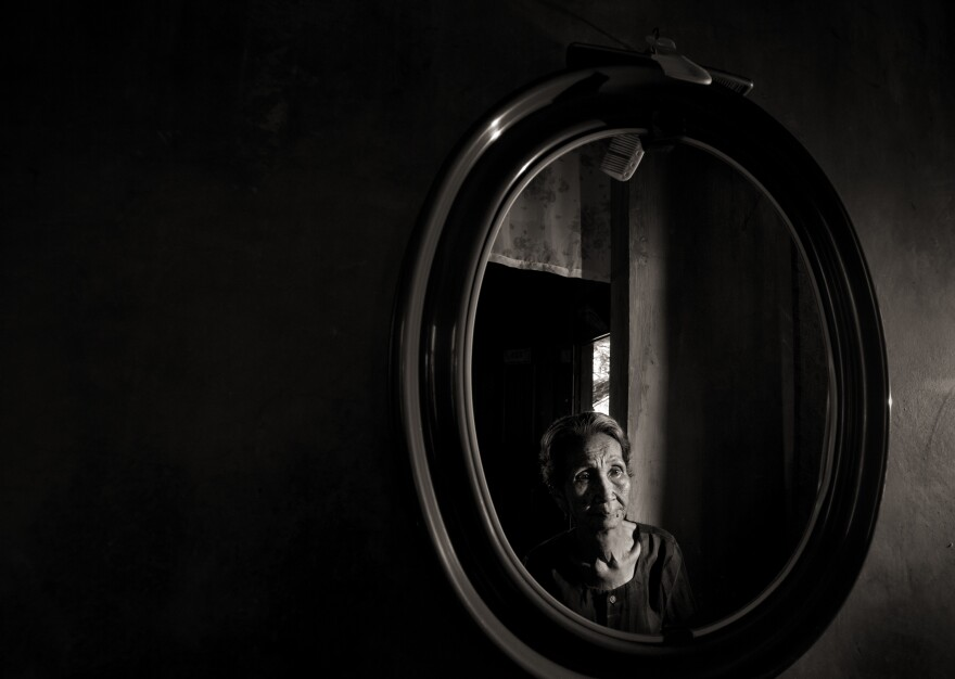 Emilia dela Cruz Mangilit is reflected in a mirror in her home in the village of Mapaniqui. Mangilit was only 15 years old when her village was shelled, then attacked by the Japanese during World War II.