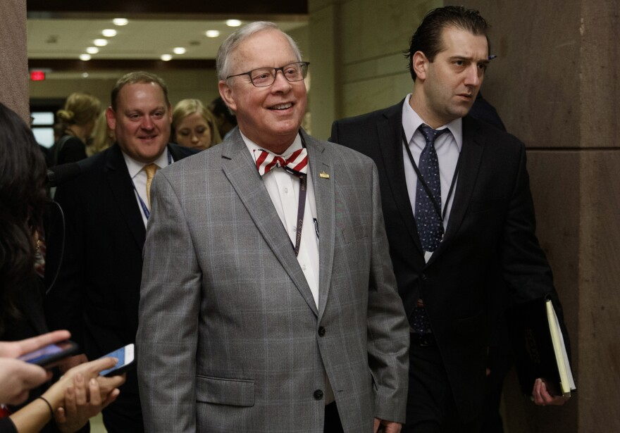 Ron Wright in gray suit with white check and red and white striped bow tie smiling as he and colleagues walk past reporters.