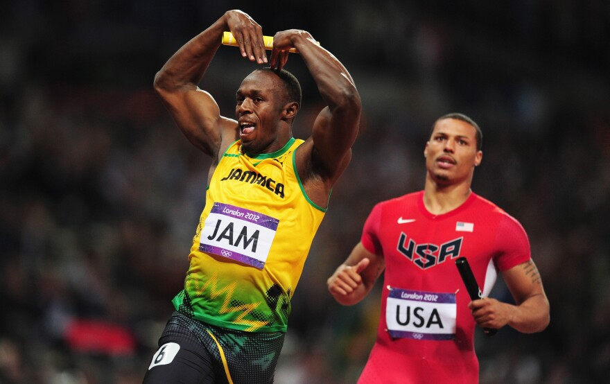 """Usain Bolt of Jamaica celebrates his relay team's world record by doing the """"mobot"""" move, made famous by Mo Farah of Britain. Bolt crossed the finish line in front of Ryan Bailey of the United States."""