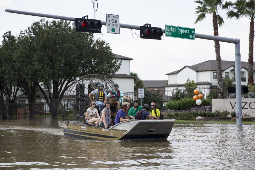 A fan boat ferries Houston residents to check on their flooded homes.