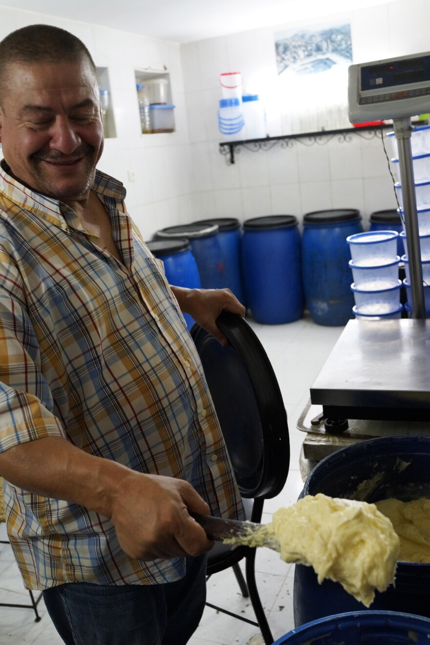 Abdelali Sheikh's family has been in the smen business for 150 years. He operates a storefront in Smen Square that's lined with blue plastic barrels and outfitted with a brass scale to measure out his products.