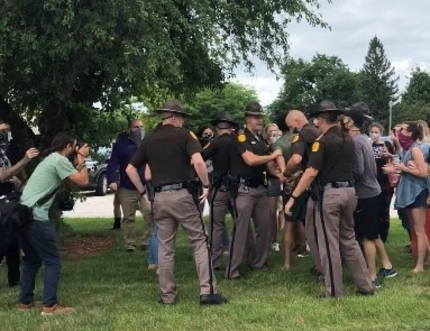 Police in brown uniforms surround protesters as people take their photos.