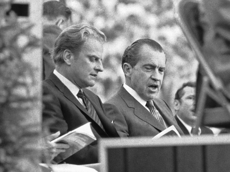 President Richard Nixon chats with the late Billy Graham, as they look over the Crusade program in Knoxville, Tenn. in 1970, a Graham-organized event that drew 75,000 people.