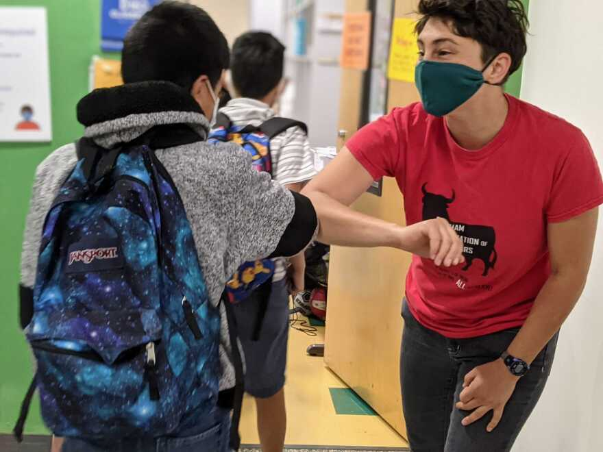 Fifth-grader Christopher Morales Perez greets his teacher Leah Erlbaum at Lakewood Elementary School as virtual students gather at the school to take their end-of-class exams.