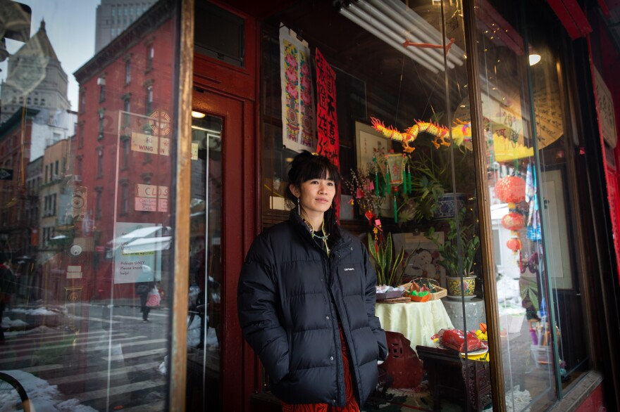 Mei Lum, the fifth generation owner of Wing on Wo porcelain shop, watches the festivities outside the store in Chinatown.