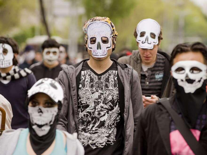Mexicans wearing masks of skulls protest against violence in the country, in Mexico City, Nov. 27, 2011. More than 50,000 people have been killed in rising drug-related violence in Mexico since December 2006.