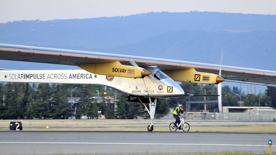 The Solar Impulse takes off from Moffett Field NASA Ames Research Center in Mountain View, Calif., Friday, as a team member rides an electric bike alongside the plane.
