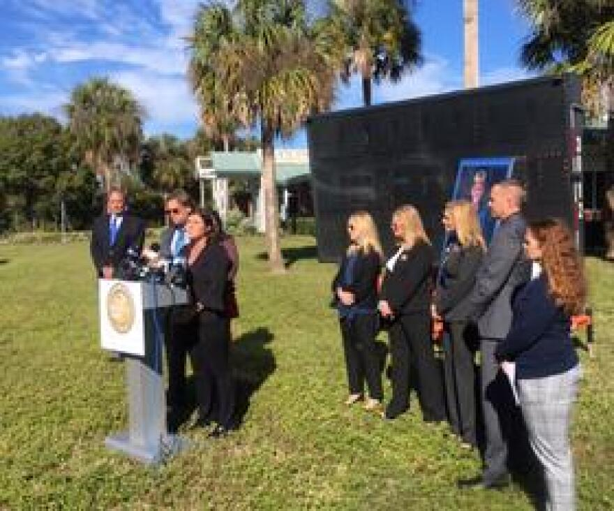 Brooke Scherer speaks next to a group of Hillsborough County  lawmakers and public school officials in front of a photo of her son, Logan