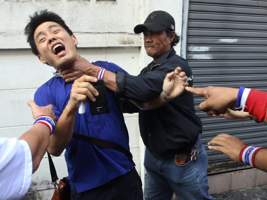 A Thai voter is attacked by an anti-government protester as he tries to enter a polling station in Bangkok, Thailand, on Sunday.