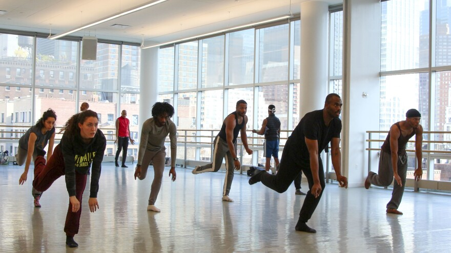 Jamar Roberts, dressed in all black in front, rehearses <em>Ode </em>with the Alvin Ailey American Dance Theater company.