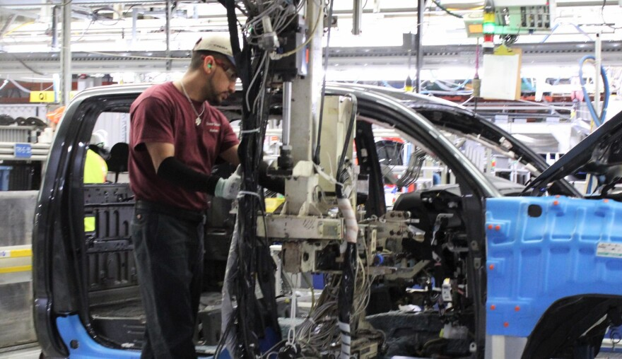 A worker uses a lift-assist device to install a dashboard at the Toyota Motor Manufacturing Texas plant in San Antonio.