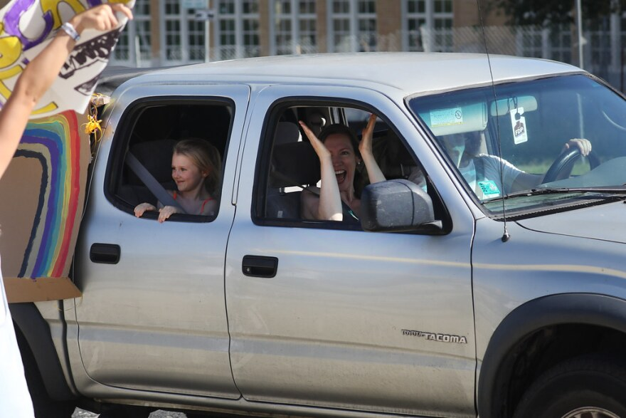 Families drive past Pease Elementary School in downtown Austin on Thursday in a parade to say goodbye to the school.