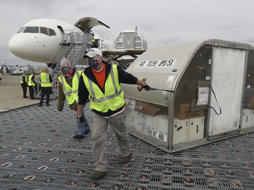 Two shipping containers holding the first doses of the Pfizer and BioNTech COVID-19 vaccine arrived at the UPS Worldport in Louisville, Ky., on Sunday.