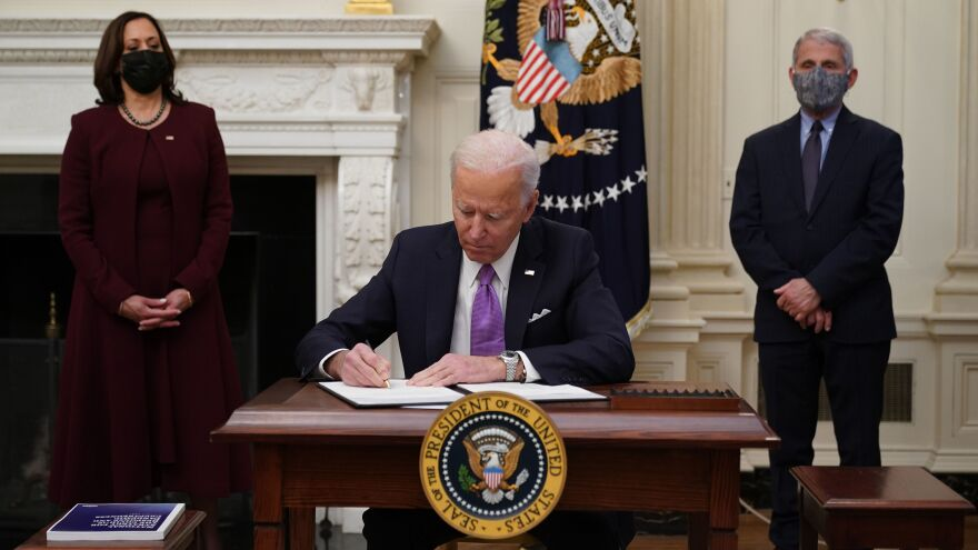 President Biden signs executive actions as part of his administration's COVID-19 response, joined by Vice President Harris and Director of NIAID Anthony Fauci in the State Dining Room of the White House on Thursday.