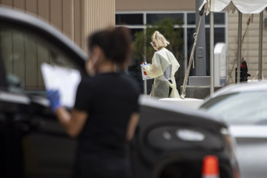 Health care workers give COVID-19 tests to people at a drive-thru clinic in South Austin.