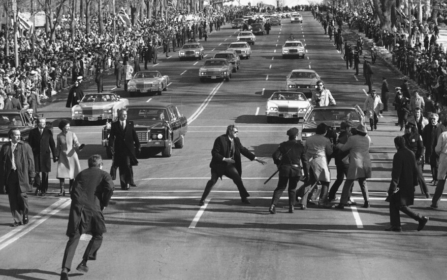 President Jimmy Carter and first lady Rosalynn watch (left) as police and Secret Service officials remove a spectator (right) who burst into the Inaugural Parade on Pennsylvania Avenue on Jan. 20, 1977.